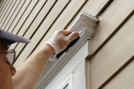 developed: Hombre al aire libre, llenando los agujeros que se desarrollaron en torno a un marco de la ventana exterior de su casa Foto de archivo