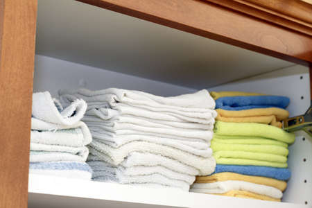 rags: A variety of folded cleaning rags on a shelf in a kitchen cabinet