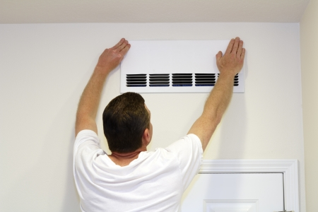 Male placing a paper cover over part of an air return intake vent to increase air return in another vent in the home   photo