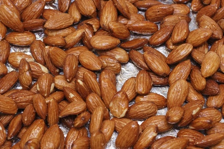 sugar maple: Close up of baked maple glazed almonds on a sheet of aluminum foil fresh out of the oven