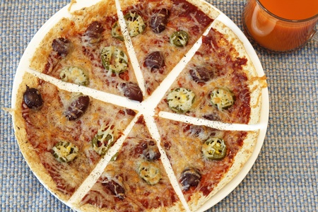 glass topped: Tortilla crust thin pizza topped with tomato paste, mozzarella cheese, jalapenos, kalamata olives and pepper near a clear glass cup of carrot juice   Stock Photo