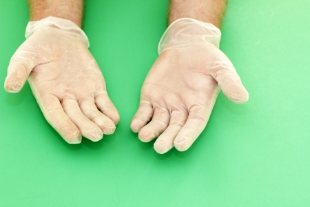 Human hands wearing powdered vinyl gloves with palms up on a green background
