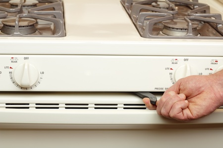 oven range: Male caucasian hand moving lever handle from left to right on self cleaning oven to start the cleaning process