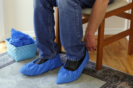 Male who just arrived in a foyer of a home for sale that he is going to tour sits in a chair putting booties on his shoes in order to protect the floors