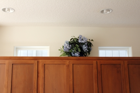 staging: Artificial hydrangea floral arrangement in a wood basket on top of kitchen cupboards to draw the eye to the windows to help people viewing a home for sale to remember it is a detached house