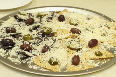 tortilla de maiz: Grano orgánico múltiple y chips de tortilla de maíz azul cubierto con queso mozzarella rallado, jalapeños y aceitunas domesticado kalamata en un molde para pizza antes de entrar al horno para fundir Foto de archivo