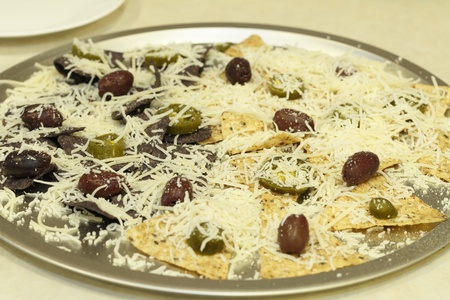 corn tortilla: Organic multi grain and blue corn tortilla chips topped with shredded mozzarella cheese, tamed jalapeno and kalamata olives on a pizza pan before going in to the oven to be melted  Stock Photo