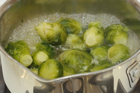 Close up of small cabbages called brussels sprouts boiling in some water in a small stainless steel saucepan on a stove  Stock Photo