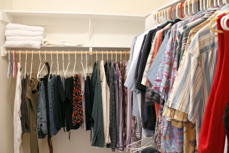 Mens wardrobe variety of pants and shirts clothing hung on plastic hangers in a home walk in closet  There are also a few bath towels on a shelf