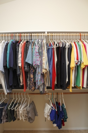 menswear: Casual menswear of dress shirts, polo shirts, t-shirts, short pants and gym shorts hanging neatly in a walk in closet of a home  Stock Photo