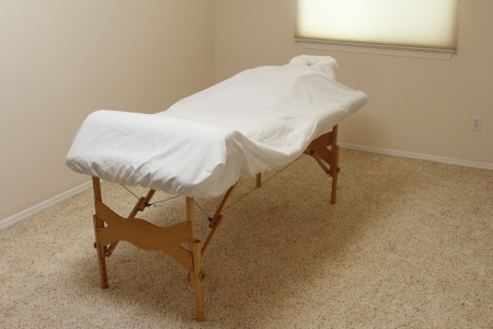 bolster: Professional wood legged massage table set up in a massage office and covered in white sheets over a bolster and body cushion during the day ready for a client