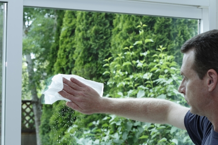 Adult male cleaning a clear glass sliding patio door with a paper towel