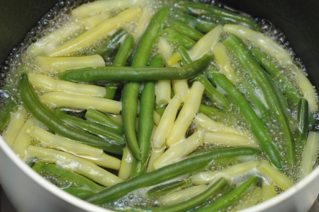 boiling: Boiling green and yellow wax beans in some water on the stove in a sauce pan