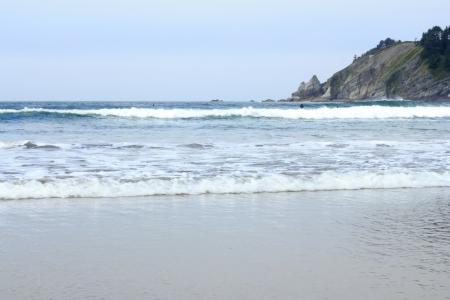 Oregon coast in the summer during the day with a few surf boarders in black wetsuits in the surf  photo