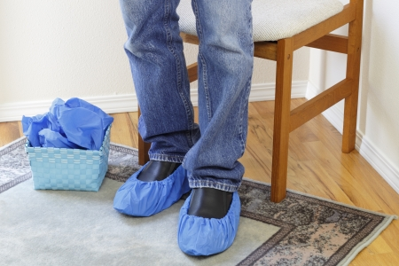 Male legs wearing jeans seen from the knees down to the floor wearing blue floor protectors called booties on both feet over a pair of black dress shoes