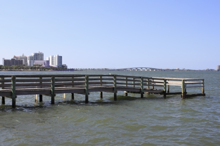 fl: Small fishing dock north of downtown Sarasota, showing in the background among other buildings the purple Van Wezel Performing Arts Hall and the John Ringling Causeway bridge on a sunny autumn day  Stock Photo