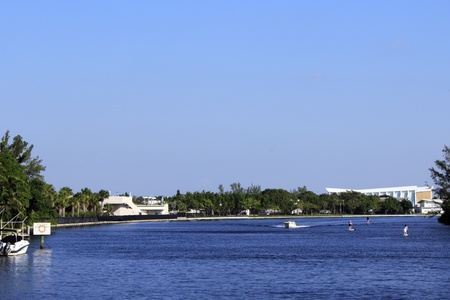 boarders: FORT LAUDERDALE, FLORIDA - OCTOBER 28: Three paddle boarders on the Middle River north of Sunrise Boulevard with a boat docked and one passing by on October 28, 2012 in Fort Lauderdale, Florida.