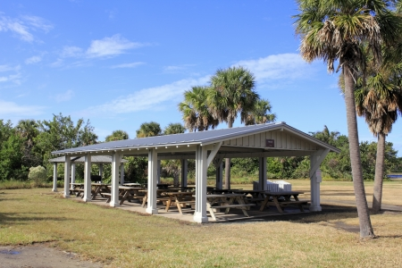 hugh: A dozen wood picnic tables covered by an open building in Hugh Taylor Birch State park in Fort Lauderdale, Florida surrounded by grass, palm and other trees and plants on a sunny autumn day
