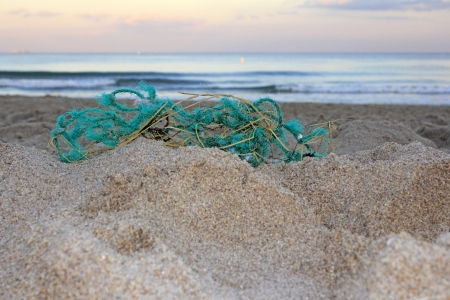 endangerment: Worn out green blue rope nylon fishing net jumbled up and washed ashore in front of a sandy atlantic coast beach at sunset emphasizing trash
