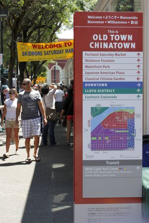 PORTLAND, OREGON - JULY 28, 2012: Chinatown directional map to area attractions and Skidmore Saturday market sign with people walking around on a sunny summer day in Portland, Oregon.