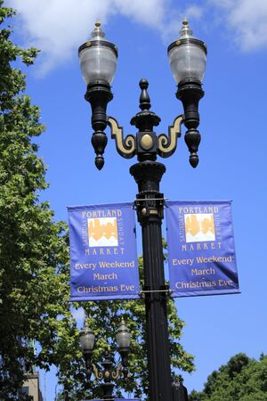 PORTLAND, OREGON - JULY 28, 2012: Two Portland Saturday Sunday Market signs hung below street lights with trees and a beautiful sunny blue sky in the background in Portland, Oregon.