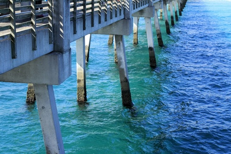 foundation: The pilings and foundation structure of an Atlantic ocean cement pier or dock seen from the pier