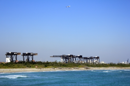 DANIA BEACH, FLORIDA - JANUARY 25, 2013: Cargo lift cranes in Port Everglades and a plane after taking off from Fort Lauderdale airport seen past the beach in Dania Beach, Florida.