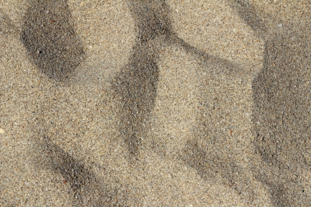 Fort Lauderdale, Florida closeup backdrop of fine grain brown sand with peaks and valleys on a sunny winter day. photo