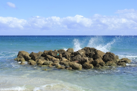 memorable: On a bright sunny day waves splash onto rocks on Deerfield Beach, Florida a beautiful scene and memorable because of it splendid beauty, unusualness and energy with its blue cloth washed ashore.