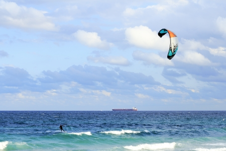 far off: FORT LAUDERDALE, FLORIDA - FEBRUARY 9, 2013  A kiteboarder sailing off the blue green Atlantic ocean coast in the morning with a red orange tanker cargo ship traveling far off in the background  Editorial