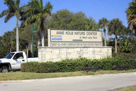 HOLLYWOOD, FLORIDA - FEBRUARY 20, 2013  Very large sign seen from the street with lots of trees and foliage in the background welcoming visitors to Center at West Lake Park on a sunny tropical day