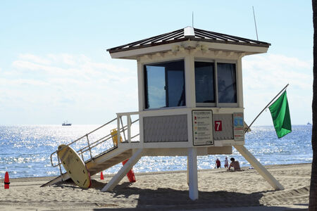 FORT LAUDERDALE, FLORIDA - FEBRUARY 5, 2013  Coastal beach lifeguard station tower 7 flying a green low hazard flag views signs, surfboards, people, boats and surfboard along sunny Atlantic ocean  Stock Photo - 25054923