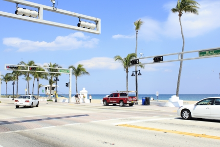 FORT LAUDERDALE, FLORIDA - MARCH 3, 2013  View of the sunny and tropical Atlantic Ocean beach seen from across State Road A1A at the end of Vistamar Street with people walking by and cars traveling