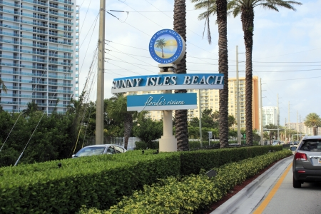 information median: SUNNY ISLES BEACH, FLORIDA - FEBRUARY 23, 2013  Sign of city between Miami and Fort Lauderdale, almost one million vacationers enjoy visiting this tropical barrier island resort community area yearly  Editorial