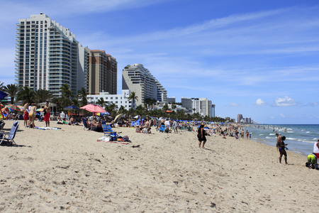 FORT LAUDERDALE, FLORIDA - APRIL 8, 2013  Long distance view of public beach filled with many people on spring break vacations, enjoying the warm sunny weather on the sand and in the Atlantic ocean