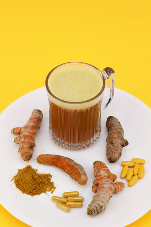Standardized extract in pills and capsules, ground powder, slightly peeled and whole rhizome roots with a blended beverage of turmeric on a white plate with an orange background