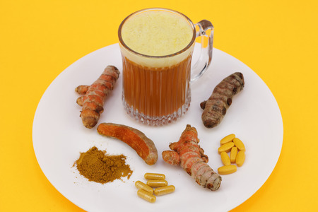 Turmeric juice beverage cup, three fresh and raw conventional rhizome roots, one turmeric root partially peeled, standardized extract capsules and tablets, along with some dry ground turmeric powder  Stock Photo