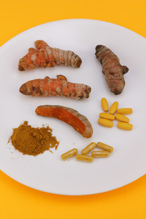 Turmeric displayed in ground powder, capsules and pills, whole raw roots or rhizomes peeled and partially peeled on a round white plate with an orange background  Banco de Imagens
