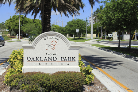 median: OAKLAND PARK, FLORIDA - MAY 7, 2013  Cement sign with buildings and tree graphic welcoming people to the city of Oakland Park, Florida on a tropical foliage street median on a sunny blue sky day  Editorial