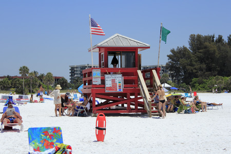 SIESTA KEY, FLORIDA - MAY 9, 2013  Red lifeguard tower flying green and American flags with a lifeguard present and lots of people around relaxing at  beautiful Siesta Beach on a very sunny, warm day