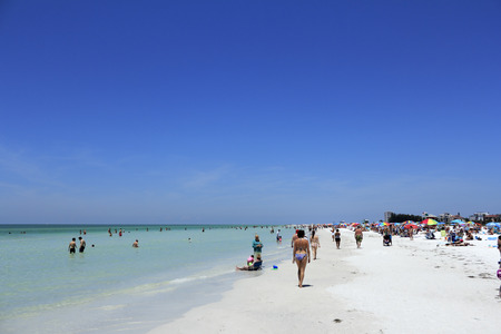 SIESTA KEY, FLORIDA - MAY 9, 2013  A colorful scene on a busy day with lots of people enjoying relaxing at the beautiful white quartz sand Siesta Beach, voted one of the best beaches in the world