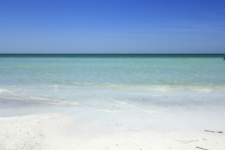 distant: Beautiful distant view of calm, clear Gulf coast turquoise tropical water and horizon seen from the white quartz sand shore of Siesta Beach under a sunny blue sky