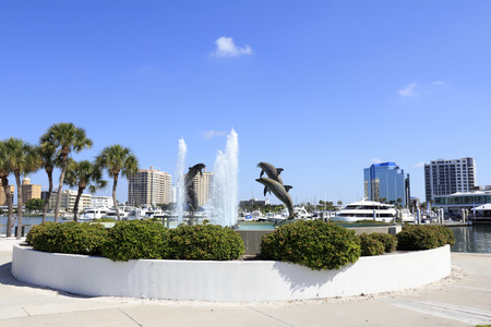 jacks: SARASOTA, FLORIDA - MAY 9, 2013: Dolphin Fountain sculpted by Steven C. Dickey, donated by Marina Jacks at the end of Sarasota Island Park and Marina with downtown buildings in the background. Editorial