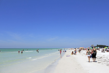 SIESTA KEY, FLORIDA - MAY 9, 2013: Many people relaxing at the sunny and beautiful white quartz sand Siesta Beach located in the Gulf of Mexico.
