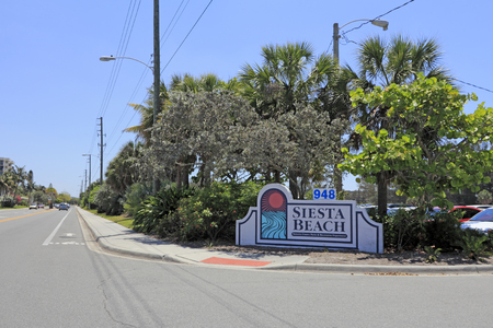 SIESTA KEY, FLORIDA - MAY 9, 2013: Siesta Beach entry sign in front of a parking lot with cars driving on Beach Road that has buildings and foliage in the background on a warm and sunny spring day.