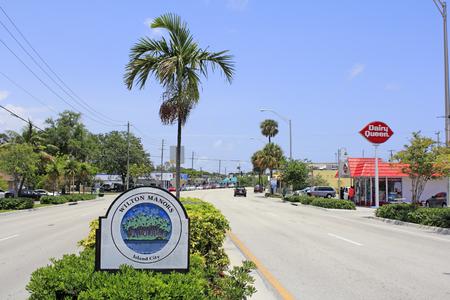 mediaan: Wilton Manors, FLORIDA - 11 mei 2013: teken dat zegt Wilton Manors en Island City met palmbomen op een eiland afbeelding in de mediaan van Wilton Drive in deze stedelijke stad van 11,9995 in 2012.