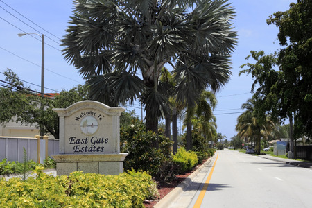 FORT LAUDERDALE, FLORIDA - JUNE 18, 2013   Stone with art welcome to East Gate Estates neighborhood sign in a beautiful, tropical foliage lined median south of Oakland Park Boulevard on a sunny day