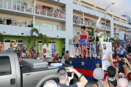 WILTON MANORS, FLORIDA - JUNE 22, 2013: Large patrioticly decorated gay parade AHF or Aids Healthcare Foundation float with two feminine performers in front and various other people and signs in back.