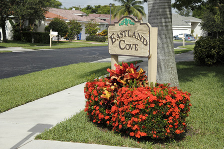 OAKLAND PARK, FLORIDA - JULY 1, 2013  Painted wood sign with orange red flowers in front of it marking the entrance to the suburban Eastland Cove neighborhood south of Prospect Road near NW 19th