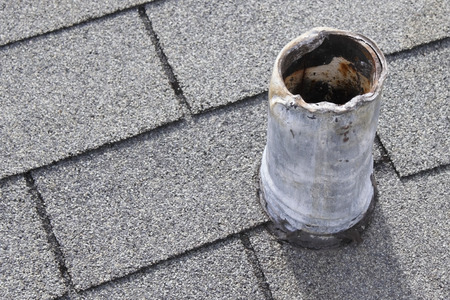 Residential short gray metal roof vent stack and black boot that shows sign of wear on top and bottom from snaking out the plumbing pipe in the past and that needs repair so there is no water damage